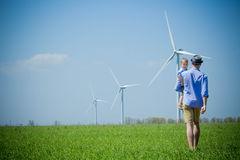 Father carries his son to the wind turbines stock image