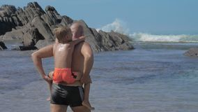Father carries little son on back walking along sea beach. Strong father carries adorable little son on back walking along sea beach against huge cliffs and blue stock video