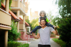 The father carries the son to school on shoulders. Little schoolboy is really like. He hugged dad's neck. A first grader is smartly dressed. Father and son royalty free stock photography