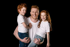 Father carrying adorable little children isolated on black Stock Photos