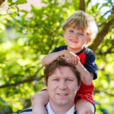 Father carrying child on his shoulders in the park. Happy little blond kid boy and young man Stock Image