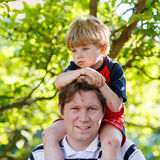 Father carrying child on his shoulders in the park. Little blond kid boy is sad Stock Photo