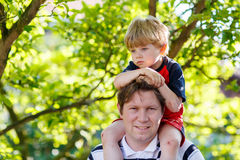 Father carrying child on his shoulders in the park Stock Photo