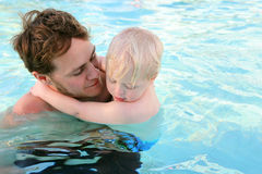 Father Carrying Child Through Water in Swimming Pool Stock Photo