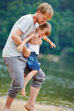 Father carrying daughter on beach Royalty Free Stock Photography