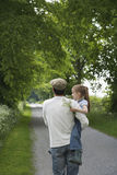Father Carrying Daughter On Country Lane Royalty Free Stock Photos
