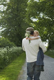Father Carrying Daughter On Country Lane Stock Photography