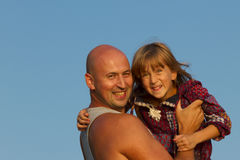 The father holds his little daughter in his arms against the background of the blue sky. Father`s Day. stock image