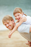 Father carrying daughter piggyback in summer Royalty Free Stock Photography