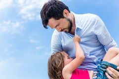 Father carrying daughter protecting her Royalty Free Stock Photos