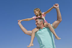 Father carrying daughter on shoulders against blue sky Stock Photography