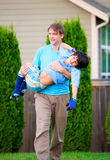 Father carrying disabled son outdoors royalty free stock photography