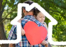 Father carrying girl holding heart shape. Overlaid with house shape royalty free stock photos