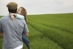 Father Carrying Happy Daughter In Field Stock Photo