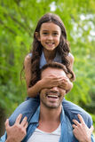 Father carrying her daughter on shoulder Stock Image