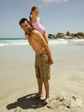 Father carrying his daughter on his back Stock Photography