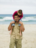 A father carrying his daughter on his shoulders. Stock Photography