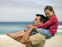 A father carrying his daughter on his shoulders. Stock Photo