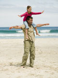 A father carrying his daughter on his shoulders. Stock Image