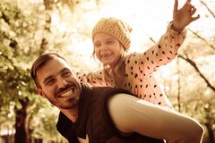 Father and daughter in park. Father carrying his daughter on piggyback i park royalty free stock photo