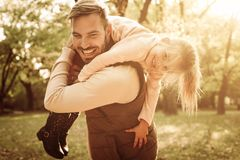 Smiling father and daughter in park. Father carrying his little daughter on shoulders stock image