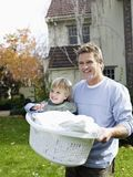 Father Carrying His Son In Basket Royalty Free Stock Image