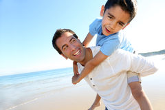 Father carrying his son on his back Royalty Free Stock Photography