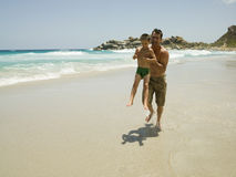 Father carrying his son and running on the beach. Royalty Free Stock Images