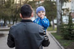Father is carrying his toddler son in arms during walk, boy is looking back with thoughtful face. Spring family walk outdoor stock images