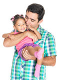 Father carrying and kissing his funny small multiracial daughter Royalty Free Stock Image