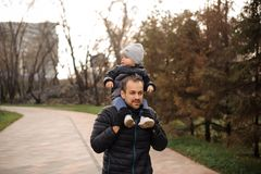 Father in carrying a little son on his shoulders. Father carrying a little son on his shoulders in the autumn park on the cloudy day Stock Photo