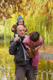Father carrying son and daughter piggybacks Royalty Free Stock Photography