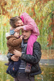 Father carrying son and daughter piggybacks Royalty Free Stock Images