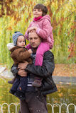 Father carrying son and daughter piggybacks Royalty Free Stock Image