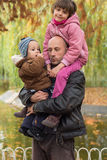 Father carrying son and daughter piggybacks Stock Image
