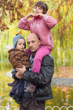 Father carrying son and daughter piggybacks Stock Photo