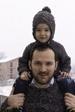Father carrying son on his back outside when it snows. Man with his boy outdoors Royalty Free Stock Photo