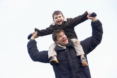 Father Carrying Son On His Shoulders. Young Father Carrying Son On His Shoulders Royalty Free Stock Photography