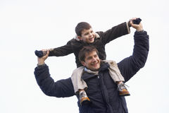 Father Carrying Son On His Shoulders. Young Father Carrying Son On His Shoulders Royalty Free Stock Photos