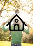 Father carrying son on his shoulders overlaid with house shape. Digital composition of a father carrying son on his shoulders overlaid with house shape Royalty Free Stock Photo