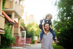 Father carrying son on his shoulders to school. Royalty Free Stock Image