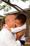 Father carrying son laughing and smiling. HIspanic father carrying son laughing and smiling royalty free stock photo