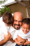Father carrying son laughing and smiling. HIspanic father carrying son laughing and smiling royalty free stock images
