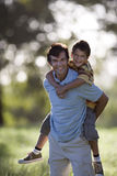Father carrying son (8-10) by piggyback in field, smiling, portrait Royalty Free Stock Photos