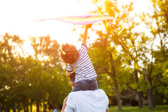 Father carrying son playing with kite Royalty Free Stock Photos