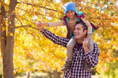 Father carrying son on shoulder against autumn tree Stock Photo