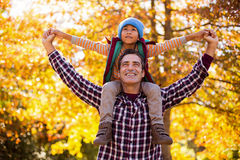 Father carrying son on shoulder against autumn trees Stock Images