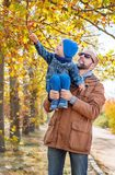 Father carrying son on shoulder at park Stock Photos