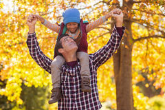 Father carrying son on shoulder at park Royalty Free Stock Photo