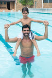 Father carrying son on shoulder in pool Royalty Free Stock Photos